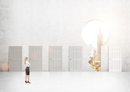 next horizon: A young businesswoman with hands crossed standing in a room with numerous closed doors, a keyhole with New York view instead of one. Side view. Concrete background. Concept of finding a way out.