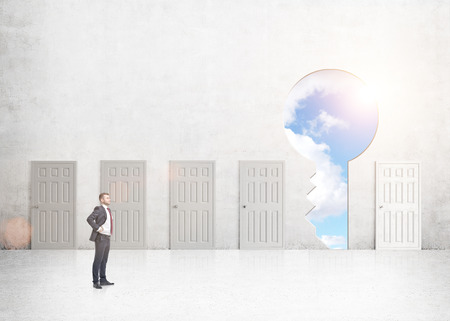 way out: A young businessman with hands on hips standing in a room with numerous closed doors, a keyhole with sky seen instead of one. Side view. Concrete background. Concept of finding a way out.