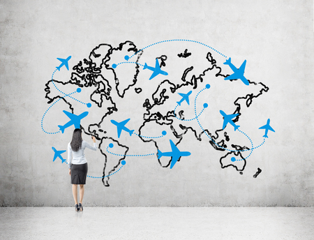 duty belt: A woman drawing a map demonstaring flight destinations around the globe on a concrete wall in front of her. Back view. Concept of flying.