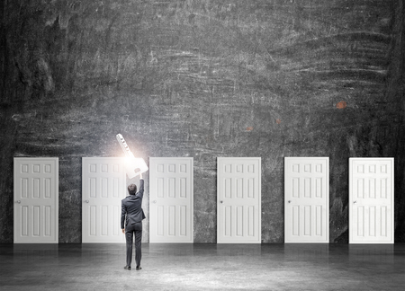 next horizon: A young businessman standing in a room with numerous closed doors as if holding a magic key in a streched hand. Back view. Black background. Concept of finding a way out. Stock Photo