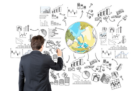 different thinking: A businessman drawing the Earth in colour surrounded by different graphs and diagrams. Back view. White background. Concept of thinking about the planet. Stock Photo