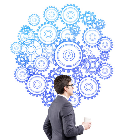 unachievable: A man with a paper cup standing at a picture of blue cogwheels. Side view. White background. Concept of creating a mechanism.