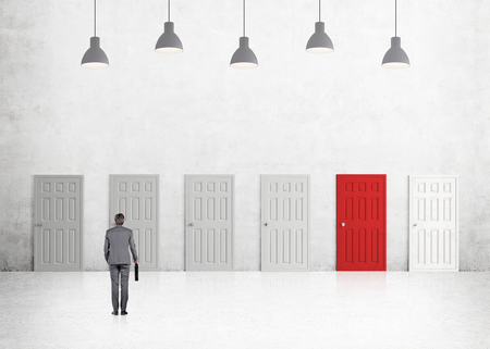 subconsciousness: A young businessman with a folder standing in a room with numerous closed doors, one of them is red. Five lamps above. Back view. Concrete background. Concept of finding a way out.