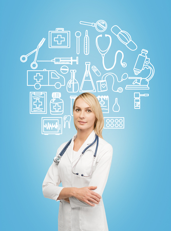 A young smiling female doctor in a white smock with hands crossed standing in front of the blue wall, many medical icons drawn on it. Front view. Concept of medical help.