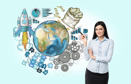 A young beautiful woman pointing at the Earth drawn in colour surrounded by graphs, rocket, cogwheels, puzzle, money. Front view. Blue background. Concept of international business. Stock Photo