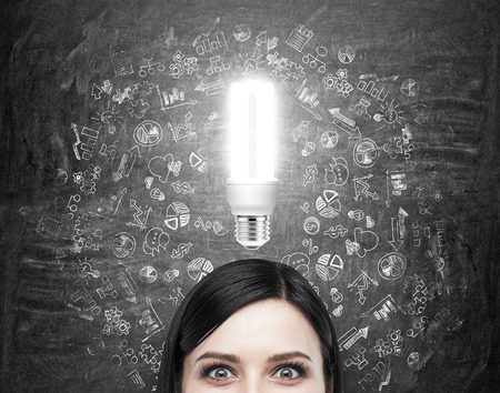 flexible business: A woman looking in front of her, black wall with many different business icons drawn around her head, a shining bulb above. Front view, only eyes seen. Concept of having an idea. Stock Photo