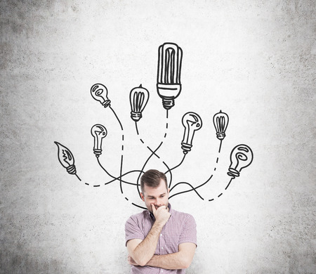 hand on chin: A young man with a hand on his chin, many different bulbs drawn around his head. Front view. Concrete background. Concept of having an idea. Stock Photo