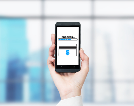 online service: A hand holding a smartphone with the word process and credit card on the screen. Blurred office at the background. Concept of paying online.