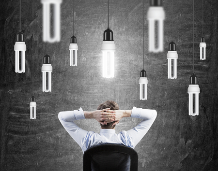 energysaving: A businessman with hands on the back of his head sitting in front of a black wall, many energy-saving bulbs hovering from above, one of them shining brightly. Back view. Concept of having an idea