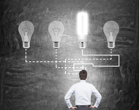energysaving: A man with hands on hips standing in front of a black wall with four connected bulbs, the energy-saving bulb shining brightly. Back view. Concept of having an idea. Stock Photo