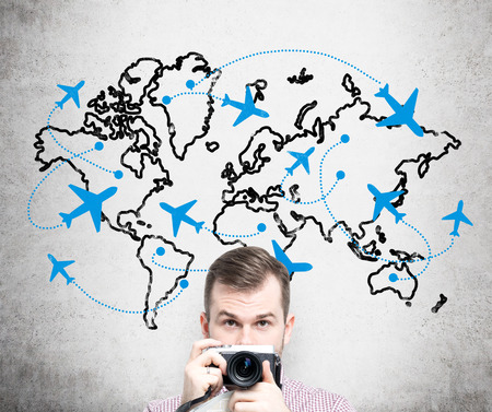 duty belt: A young man with a camera standing in front of a concrete wall with a world map and planes drawn on it behind his back. Front view, only head. Concept of flying. Stock Photo