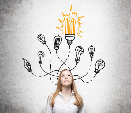 energysaving: A pretty young woman looking up, many different bulbs drawn around her head, the biggest energy-saving bulb is yellow. Front view. Concrete background. Concept of having an idea. Stock Photo