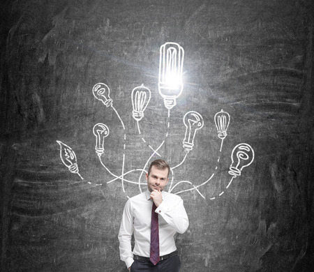 flexible business: A young businessman with a hand on his chin standing, many different bulbs drawn around his head, one of them shining. Front view. Black background. Concept of having an idea.
