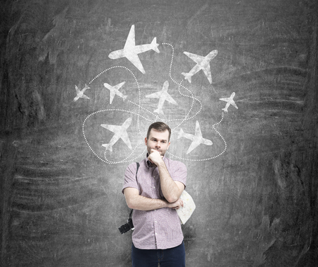 duty belt: A young man with a camera and a hand to the chin standing in front of a blackboard with planes drawn on it behind his back, thinking about traveling. Front view. Concept of flying.