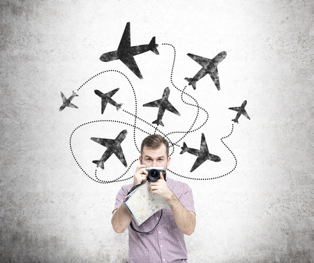 duty belt: A young man with a camera and a map standing in front of a concrete wall with planes drawn on it behind his back. Front view. Concept of flying.