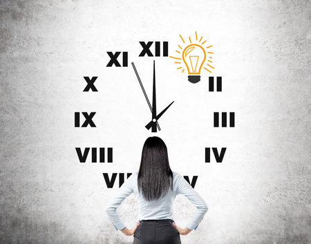 career timing: A woman with hands on hips standing in front of a clock painted on a concrete wall, a bulb instead of 1 on the clock. Back view. Concept of having and idea on time.