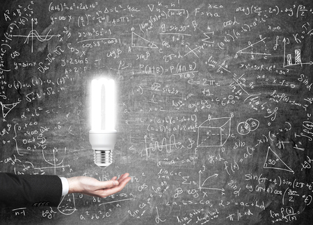 energysaving: A hand as if holding an energy-saving bulb shining brightly, many science icons drawn on the black wall behind it. Concept of having an idea.