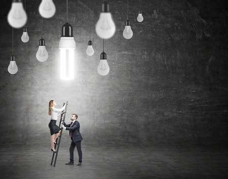 energysaving: A woman climbing a ladder, a man helping her in front of a black wall, many different bulbs hovering from above, the energy-saving bulb shining brightly. Back view. Concept of having an idea. Stock Photo