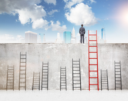 pay wall: A businessman with hands in pockets standing on a concrete wall separating him from New York. Several ladders of different size at the wall, blue sky above. Concept of reaching aim.