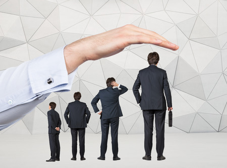 tallness: Four businessmen of different size arranged by tallness standing under a huge hand. Grey geometric background. Concept of career growth.