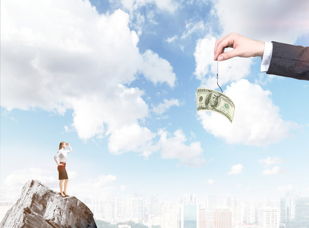 A hand holding a one-hundred dollar banknote on a thread, a young businesswoman on the rock looking at it. City and blue sky at the background. Concept of motivation.