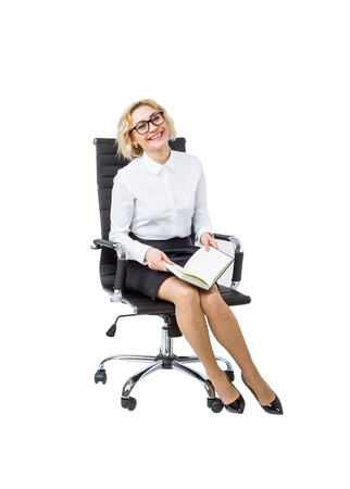 postgraduate: A beautiful smiling businesswoman with a book sitting on the castor chair. Side view. Isolated. Concept of work.