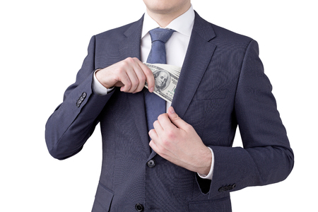 putting money in pocket: A man putting a one hundred dollar banknote into the chest pocket. No head seen. Isolated. Concept of earning money.