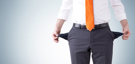 A businessman with an orange tie turning his empty pockets inside out. Front view, no head. Grey background. Concept of bankruptcy. Stock Photo