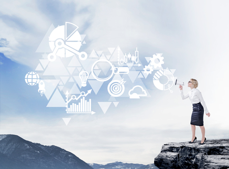 informing: A young pretty businesswoman standing on the rock and shouting in a loudspeaker, different icons flying out of it. Side view, blue sky and mountains at the background. Concept of informing.
