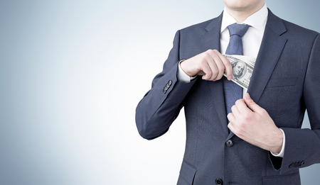onehundred: A businessman putting a one-hundred dollar banknote into the chest pocket. Grey background. Front view, no head. Concept of getting money.