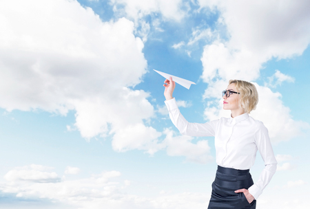 self assured: A woman with a paper plane ready to let it go. Side view. Blue sky at the background. Concept of starting a new project. Stock Photo