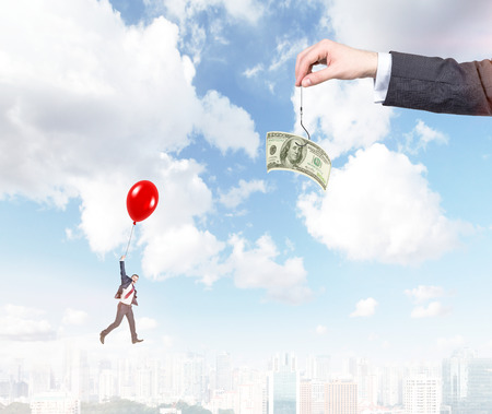onehundred: A hand holding a one-hundred dollar banknote on a thread, a young businessman flying on a red balloon to it. City and blue sky at the background. Concept of motivation.