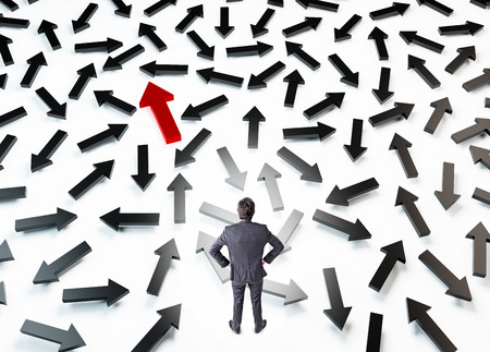 specialization: A businessman with hands on hips standing on the white floor full of black arrows in different directions, one of them is red. Top view. Concept of choice.
