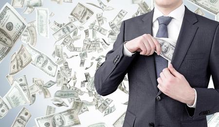 money flying: Un hombre de negocios que pone un billete de cien dólares en el bolsillo del pecho. Vuelo del dinero en el fondo. Vista frontal, sin cabeza. Concepto de conseguir dinero.