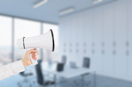 advertising space: A hand holding a white loudspeaker. Side view. Blurred office at the background. Concept of informing