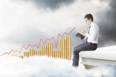 grafica de barras: Un joven sentado en el borde de la cubierta y la lectura de un libro. Vista lateral. Las nubes oscuras, gráficos de barras de monedas y gráfico de rojo en el fondo. Concepto de estudiar