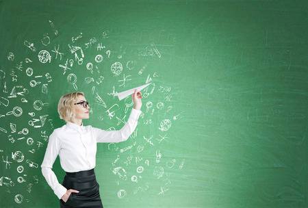 educaton: A woman with a paper plane ready to let it go, science icons drawn around her on the blackboard. Side view. Green background. Concept of starting a new project. Stock Photo