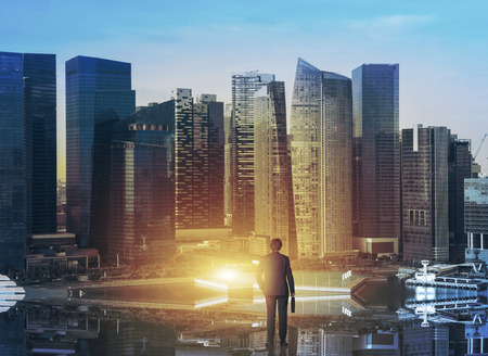 at the start: A businessman with a case having just arrived to Singapore. City in the sunrise. Back view. Concept of a new start. Stock Photo