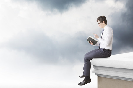 man studying: A young man sitting on the edge of the roof and reading a book. Side view. Dark clouds at the background. Concept of studying Stock Photo