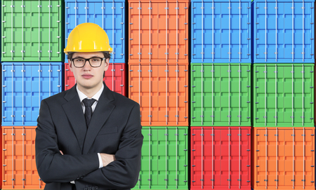 differnt: Businessman in yellow helmet with hands crossed, many sea containers of differnt colours behind. Front view. Concept of shipping. Stock Photo