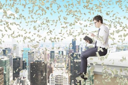 may�sculas: Un joven sentado en el borde de la cubierta y la lectura de un libro, el dinero que caen desde arriba. Vista lateral. Nueva York, en el fondo. Concepto de estudiar Foto de archivo