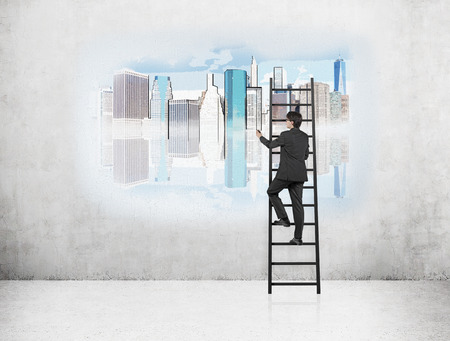 Businessman on ladder drawing image of New York on concrete wall. Concept of NY dream.