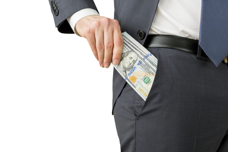 putting money in pocket: A man putting a one hundred dollar banknote into the chest pocket. Only trousers seen. Isolated. Concept of earning money.