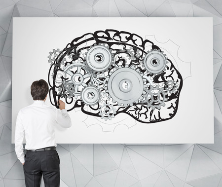 mental work: Businessman drawing image of brain with gears on white poster. Back view. Grey background. Concept of mental work.