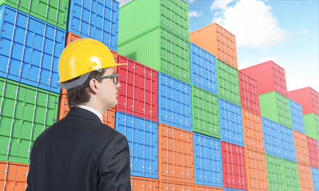 differnt: Businessman in yellow helmet looking at many sea containers of differnt colours stocked. Blue sky above. Concept of shipping.