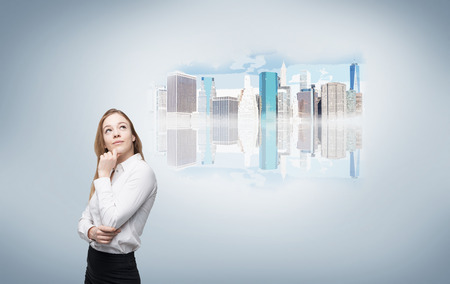 hand on chin: Young businesswoman with hand on chin thinking, picture of New York to the right, grey wall. Concept of NY dream.