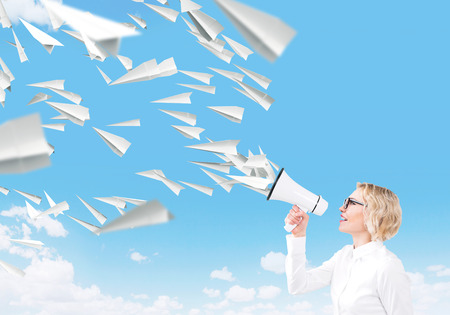 informing: Beautiful woman with white loudspeaker, paper planes flying from it. Side view. Sky at background. Concept of informing.