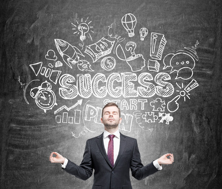 career timing: Businessman in posture of meditation standing in front of black chalk wall with business development pictures on it. Front view. Concept of success in business Stock Photo