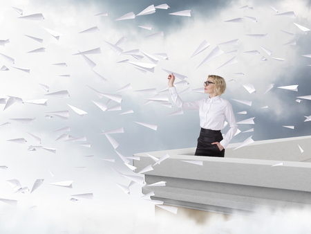 trajectory: Businesswoman with paper plane on roof, grey sky and clouds at background, paper planes flying everywhere. Concept of difficulty for new start. Stock Photo