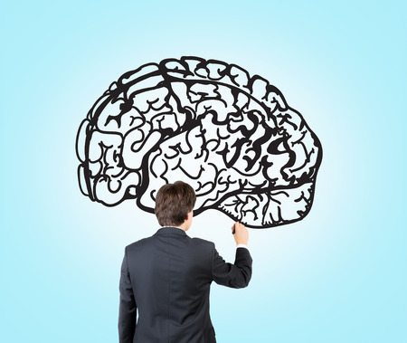 mental work: Businessman drawing image of brain on blue wall. Back view. Concept of mental work.